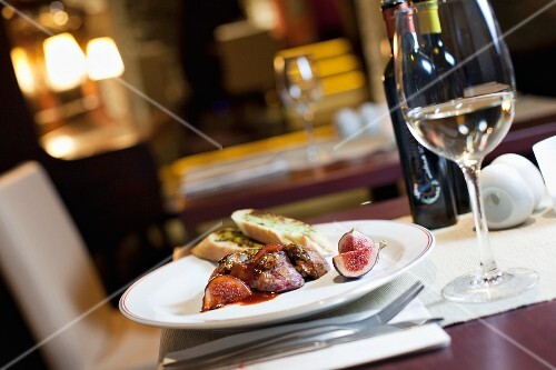 a view on the interior of the restaurant, a table with wine and a dish of grilled liver with figs