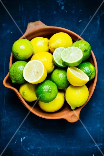Fresh lemons and limes in an earthenware dish