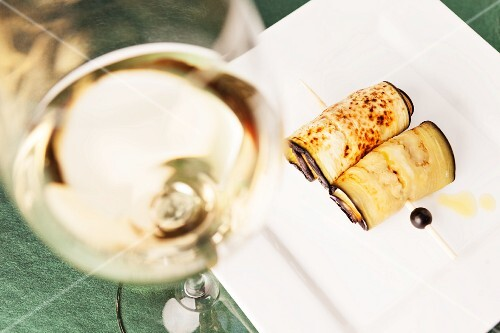 Fried aubergine rolls and a glass of white wine