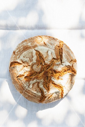 A rustic loaf of country bread on a sunny table