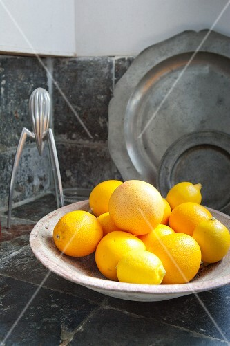Ceramic dish of lemons, pewter plates leaning against wall and designer lemon squeezer on stone-tiled kitchen worksurface