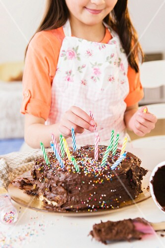 A girl sticking birthday candles into a chocolate cake
