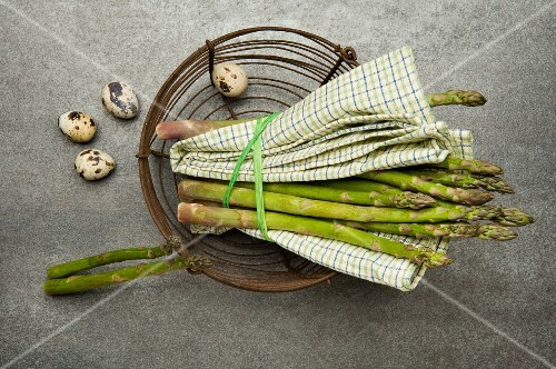 Green asparagus and quail's eggs in a wire basket