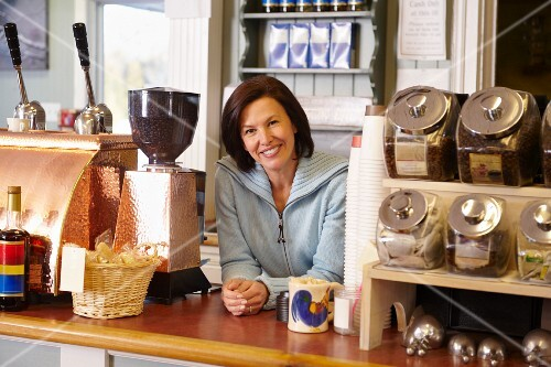 A sales assistant behind the counter of an old fashioned coffee shop