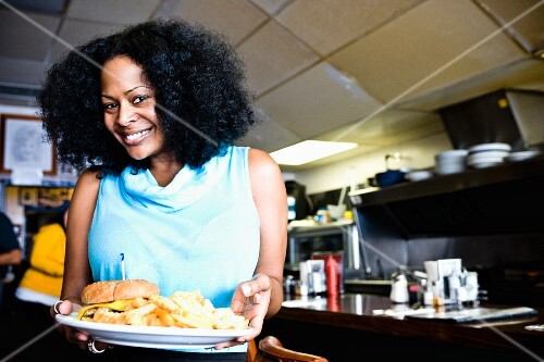 A smiling African-American woman holding a burger on a plate