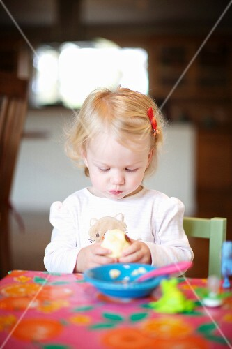 A little girl eating at a table