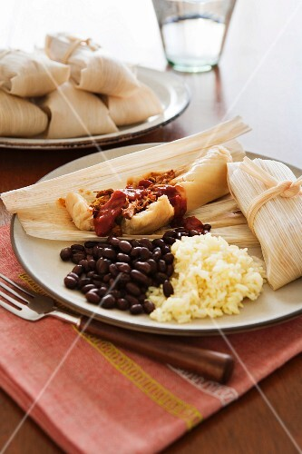 Pamonha (Stuffed corn leaves, Brazil) with beans and rice