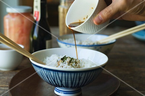 A person pouring sauce onto rice