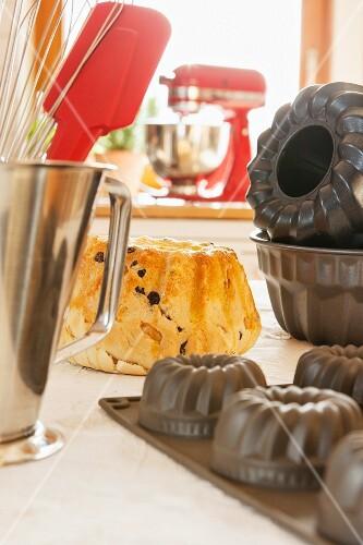 A Bundt cake, various baking tins and kitchen utensils