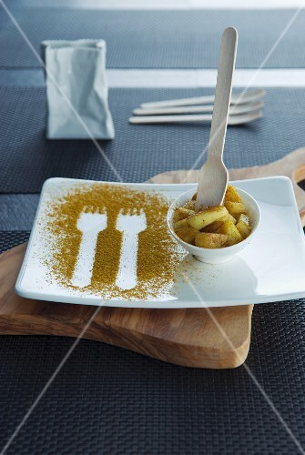 Fork prints in curry powder on a plate with a bowl of curried potatoes