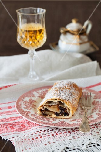 Apple strudel on a plate with glass of wine