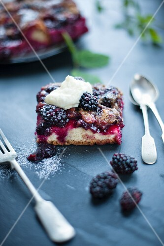 A slice of blackberry cake with cutlery , garnished with cream.