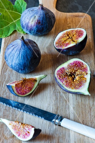 Cut fresh figs on a wooden board with a knife and fresh fig leaf.