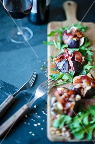 Grilled figs with blue cheese and parma ham on a wooden board with rocket salad.