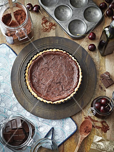 Chocolate tart surrounded by ingredients (seen from above)