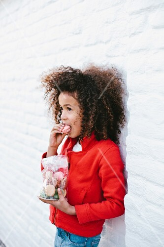 A girl leaning on a wall and eating a bag of macarons
