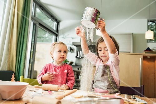Two children baking biscuits in a kitchen