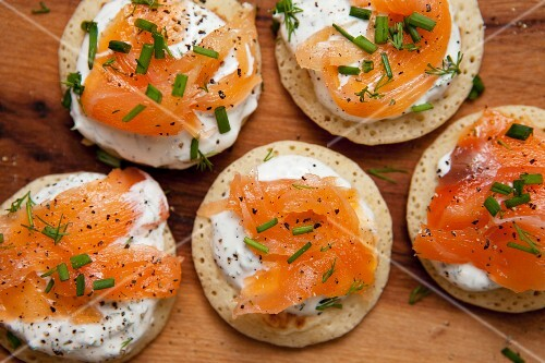 Blinis topped with smoked salmon, sour cream and chives on a wooden board