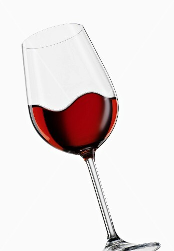 A tilted glass of red wine, moving