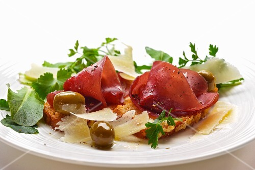 bresaola on bruschetta with parmesan, olives and sald