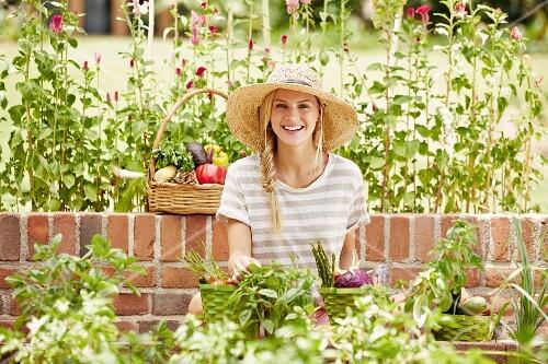 Caucasian woman picking vegetables in garden