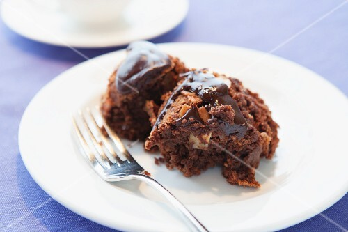 A slice of chocolate cake with nuts on a plate