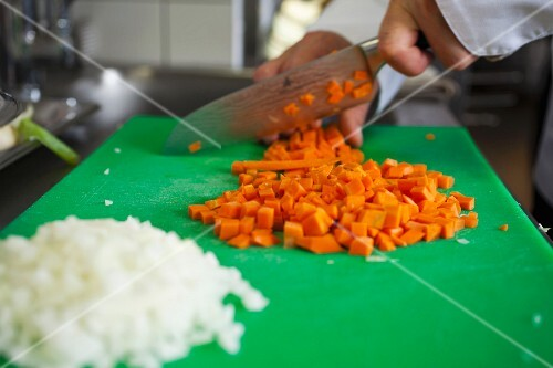 preparation of a typical Czech dish called Svickova, cutting of carrots and onions