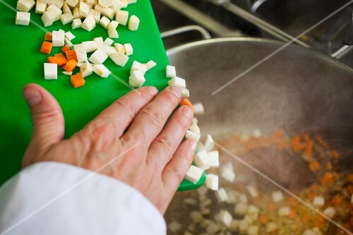 a hand puts pieces of carrots and onions in a pot with tenderloin beef, for a typical Czech dish called Svickova