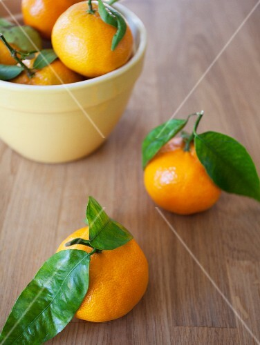 A bowl of clementines with leaves and two next to it
