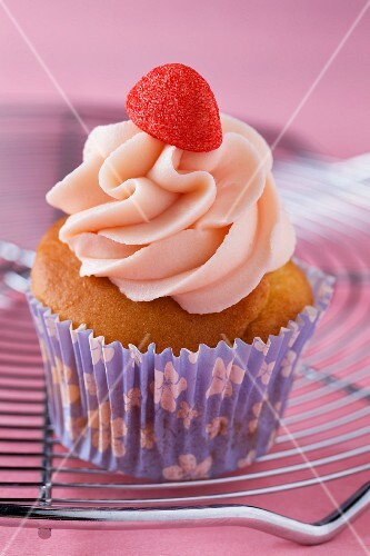 A cupcake decorated with strawberry cream and a strawberry bonbon