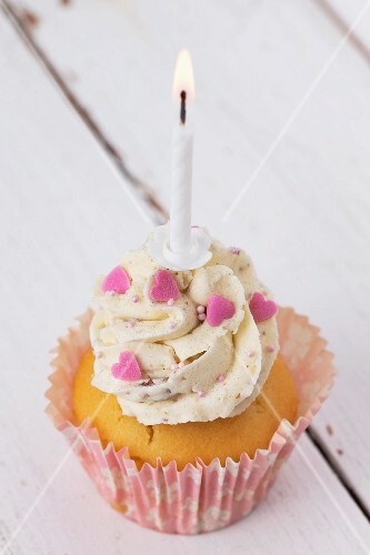 A cupcake decorated with buttercream, pink hearts and a birthday candle