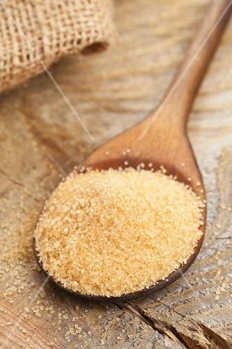 Unrefined cane sugar on a wooden spoon