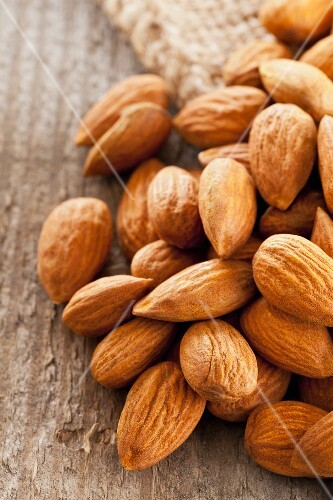 A pile of almonds on a wooden surface
