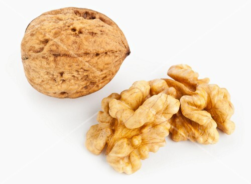 A whole walnut in its shell and two walnut halves