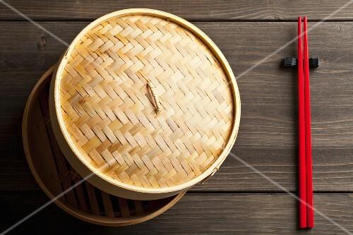 A bamboo steamer and chopsticks