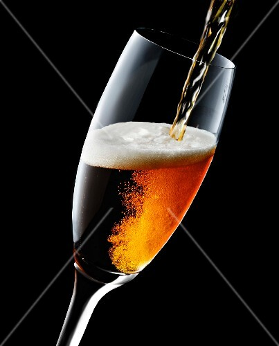 Cold Beer Pouring From a Bottle into a Glass; Overflowing