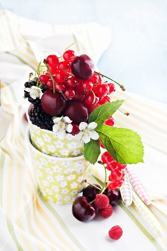 Various berries and cherries in a cup