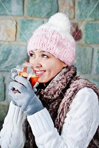 Frau trinkt Wintertee mit Apfel und Zimt