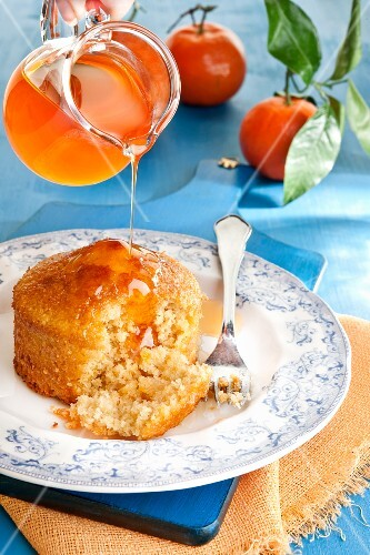 Mandarin syrup being poured over a mini cake