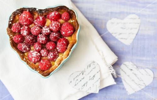 A raspberry tart in a heart-shaped baking tin