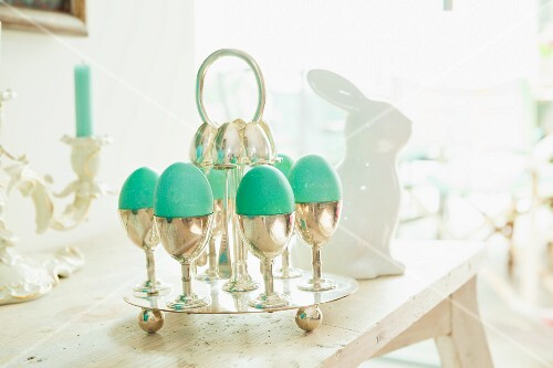 Green Easter eggs in silver egg cups on a table laid for Easter