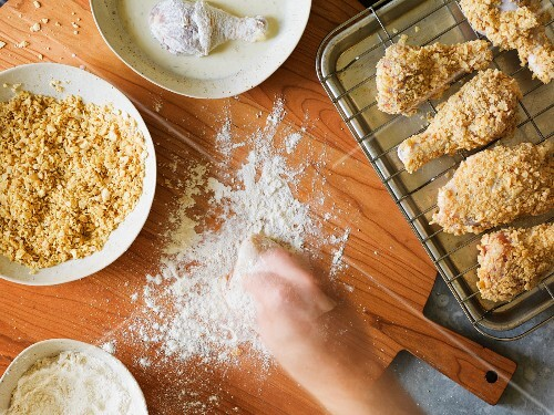 Preparation for breading baked chicken legs in a crushed potato chip crust with an hand in action sprinkling flour