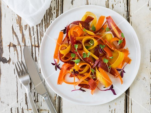 Bright yellow, orange and red carrot salad with micro-greens on a white plate sitting on an antique white wood surface
