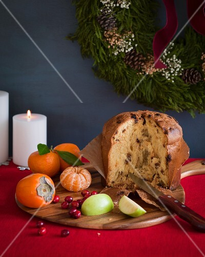 Italian panettone cut open on a cutting board with fruit on a red tablecloth with white candles and a wreath in the background