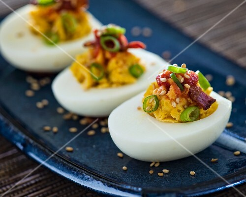 Three deviled egg halves with green onions and bacon sitting on a blue Asian-style plate