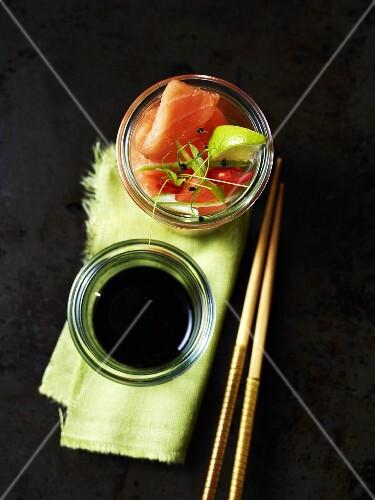 Salmon sashimi and soya sauce on small glass bowls (Japan)