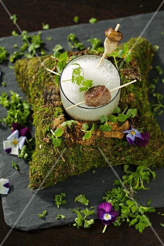Foam soup with porcini mushrooms and meatballs on a bed of moss