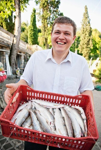 A man holding a red crate of fresh fish
