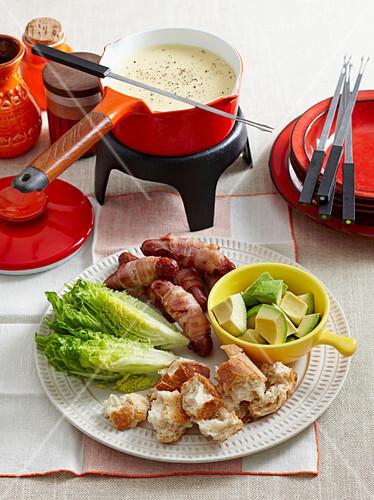 Käsefondue mit Brotstücken, Avocado, Romanasalat und Würstchen im Speckmantel
