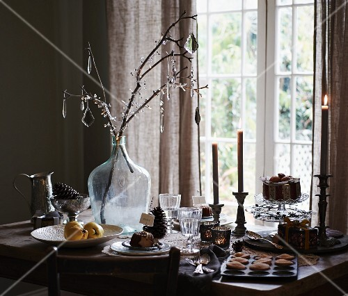 Glass decorations hanging on branches in demijohn on festively set table
